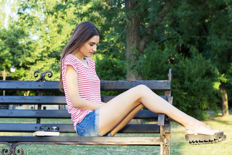 Smutna rozważna młoda dziewczyna siedzi samotnie na ławce outdoors Ładnej kobiety myślący zamyślenie Czuciowy ból nadzieja smucen zdjęcia stock