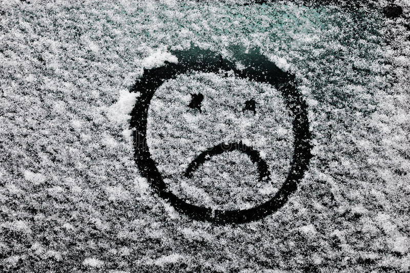 Smutna smiley twarz rysująca na śnieżystym szkle fotografia stock