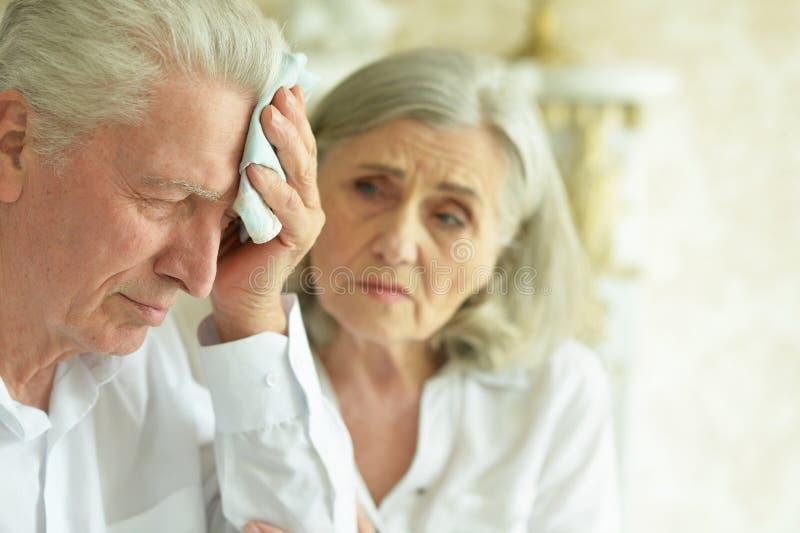 Smutna starsza para w domu, mężczyzna z migreną fotografia stock