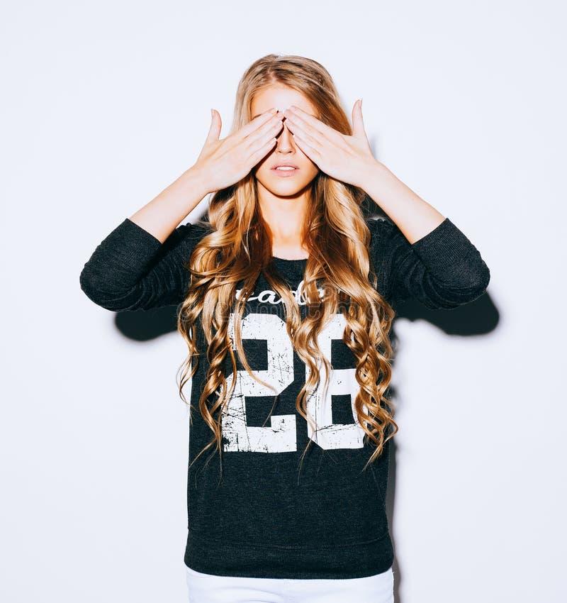 Smutnego stylu życia portreta piękna blond dziewczyna zamyka oczy z jej rękami w bluzie sportowa i biel skrótach, salowy kolor ci zdjęcie stock