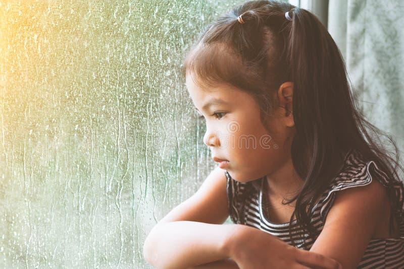 Smutnej azjatykciej małej dziewczynki przyglądający outside przez okno obrazy royalty free