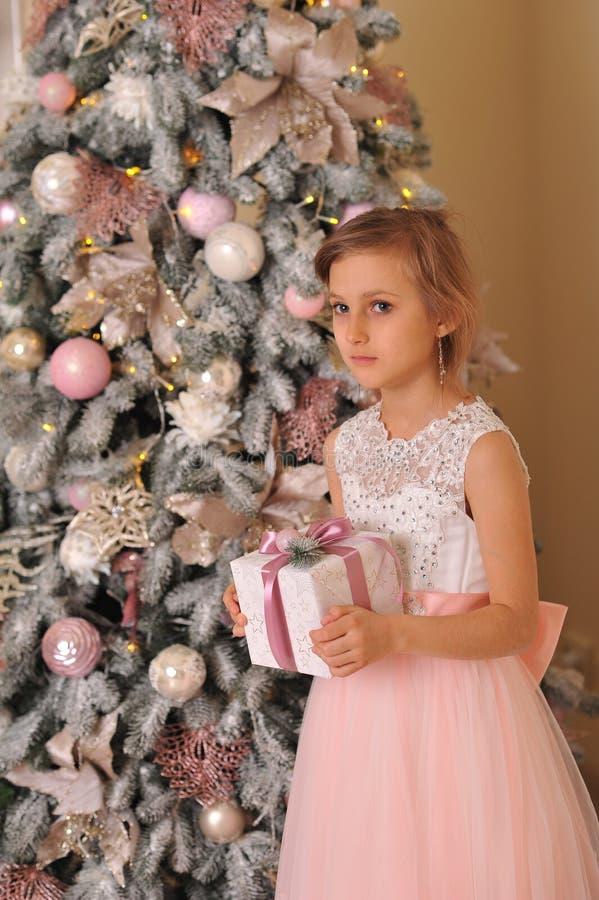 Smutni dziewczyna stojaki blisko choinki z prezentami fotografia royalty free