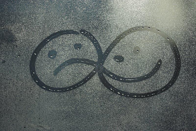 Smutni i rozochoceni uśmiechy na mokrym szkle obraz stock
