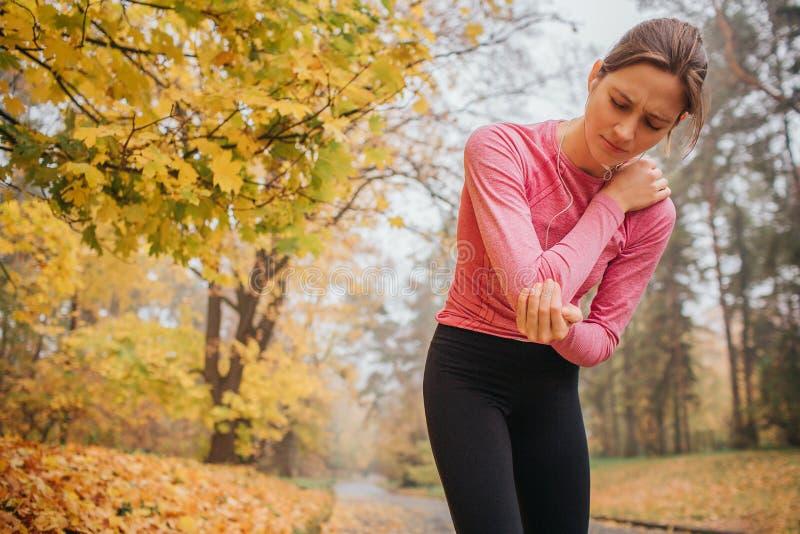 Smutni i wzburzeni młodzi żeńscy jogger stojaki w jesieni parkują ręki na szyi i trzymają Czuje ból tam Młoda kobieta cierpi obrazy stock
