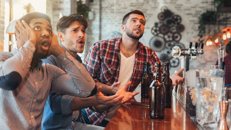 Smutni męscy przyjaciele ogląda futbol przy barem obraz royalty free