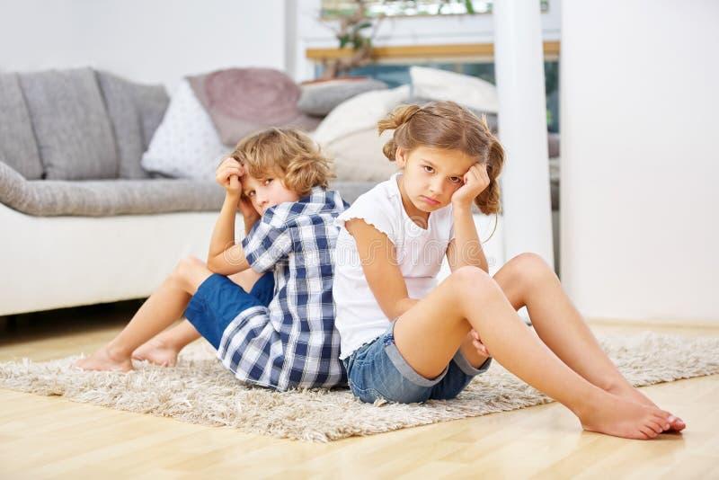 Smutni rodzeństwa siedzi w domu fotografia stock