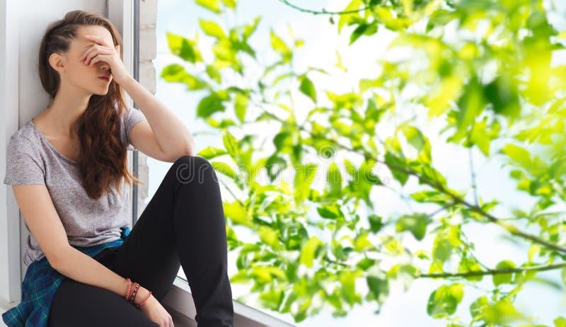 Smutny ładny nastoletniej dziewczyny obsiadanie na windowsill obrazy stock