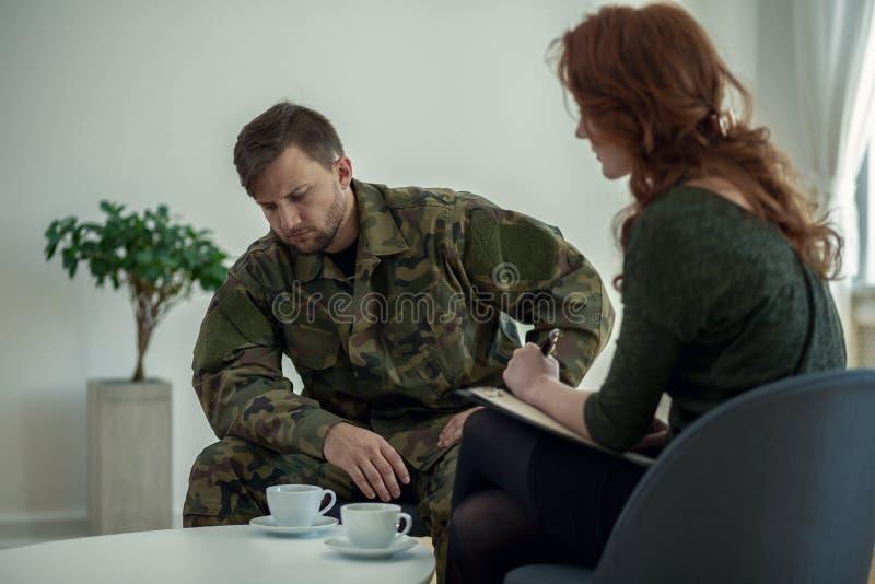 Smutny żołnierz w mundurze podczas spotkania z psychoterapeuta w biurze zdjęcie royalty free