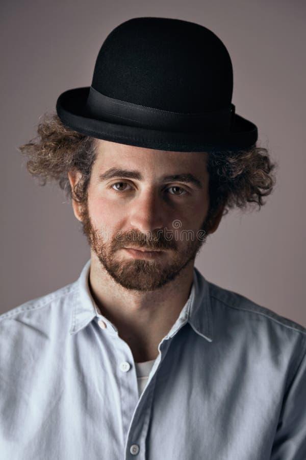 Smutny brodaty mężczyzna z kędzierzawym włosy w czarnym kapeluszu obrazy royalty free