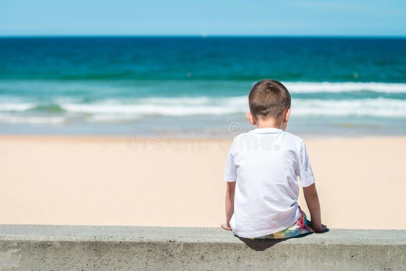 Smutny chłopiec obsiadanie przy plażą obrazy royalty free