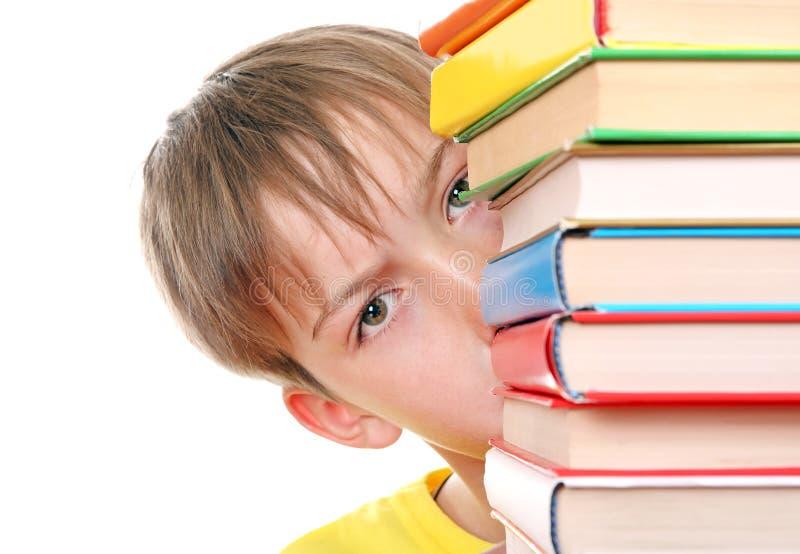 Smutny dzieciak za książkami obraz royalty free
