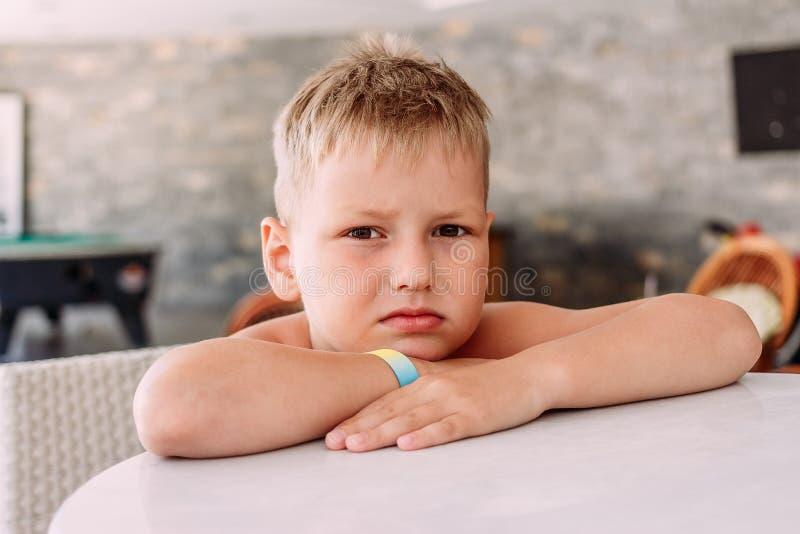 Smutny dziecka obsiadanie przy stołem w lato kawiarni obraz stock