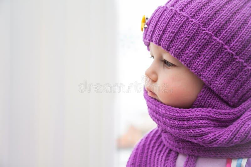Smutny dziecko patrzeje w okno podczas zimnego zima dnia w ciepłym odziewa fotografia stock