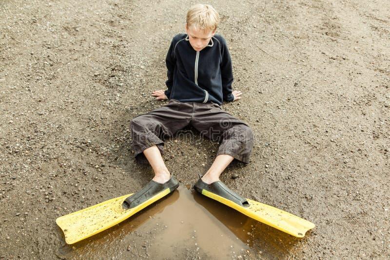 Smutny dziecko w nurkowych flippers przy kałużą zdjęcie stock