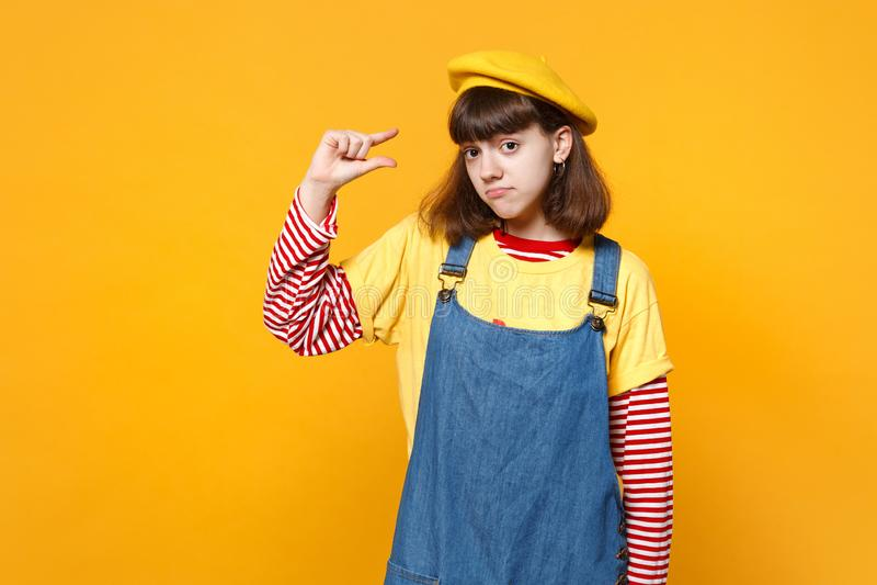 Smutny dziewczyna nastolatek w francuskim berecie, drelichowi sundress gestykuluje demonstrujący rozmiar z workspace odizolowywaj obrazy stock