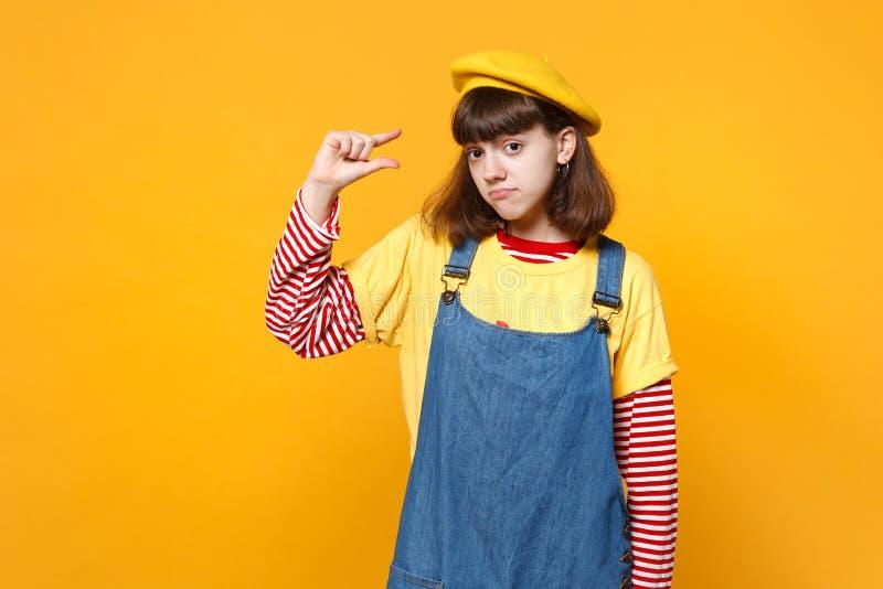 Smutny dziewczyna nastolatek w francuskim berecie, drelichowi sundress gestykuluje demonstrujący rozmiar z workspace odizolowywaj obraz royalty free