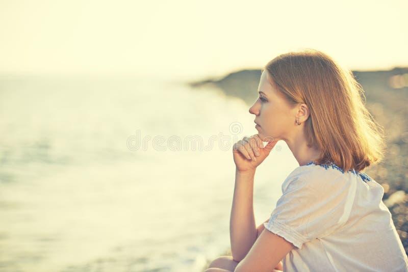 Smutny dziewczyny obsiadanie na plaży i spojrzenia w odległość przy se obraz royalty free