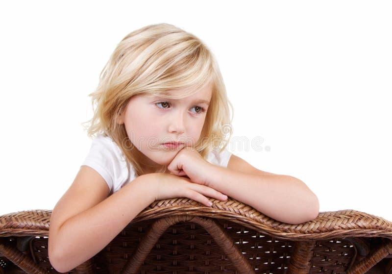 Smutny dziewczyny obsiadanie w krześle zdjęcia stock