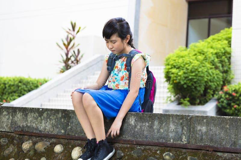 Smutny dziewczyny obsiadanie w szkole fotografia stock
