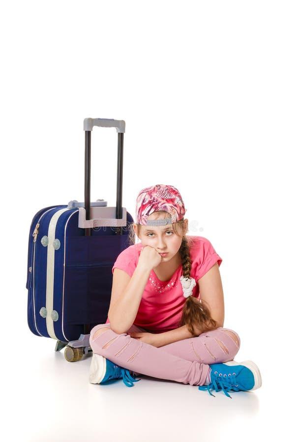 Smutny dziewczyny obsiadanie z podróży torbą zdjęcia stock