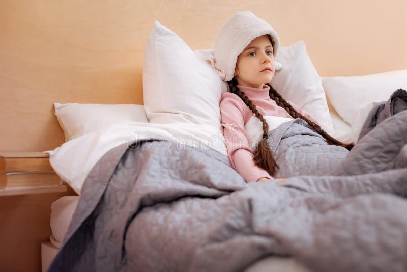 Smutny dziewczyny obsiadanie z ręcznikiem na jej głowie zdjęcia stock
