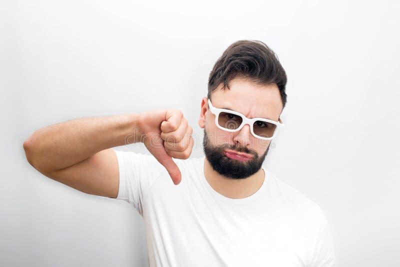 Smutny i nieszczęśliwy brodaty młodego człowieka stojak i trzyma jego dużego kciuka puszek Nie lubić film Facet utrzymuje policzk obraz stock