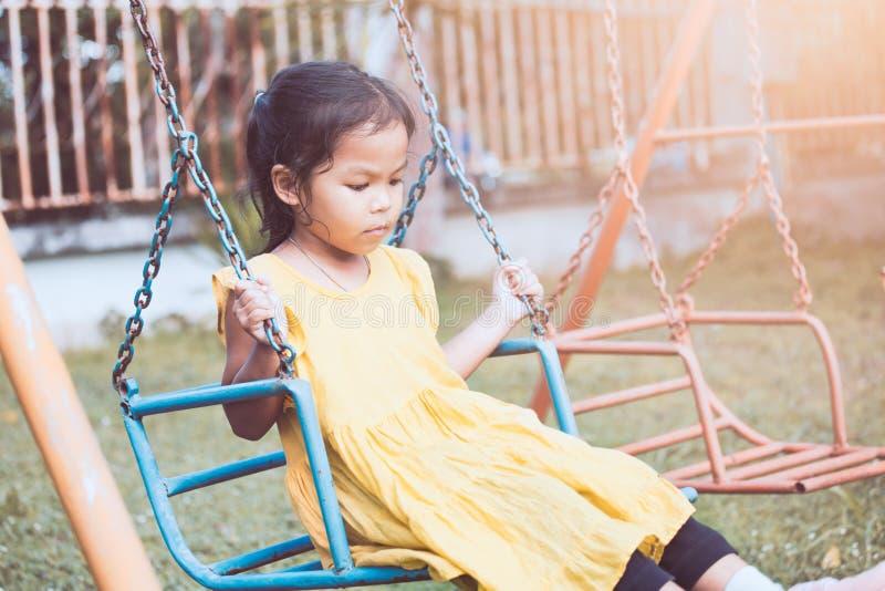 Smutny i osamotniony azjatykci małe dziecko dziewczyny obsiadanie na huśtawkach zdjęcia royalty free