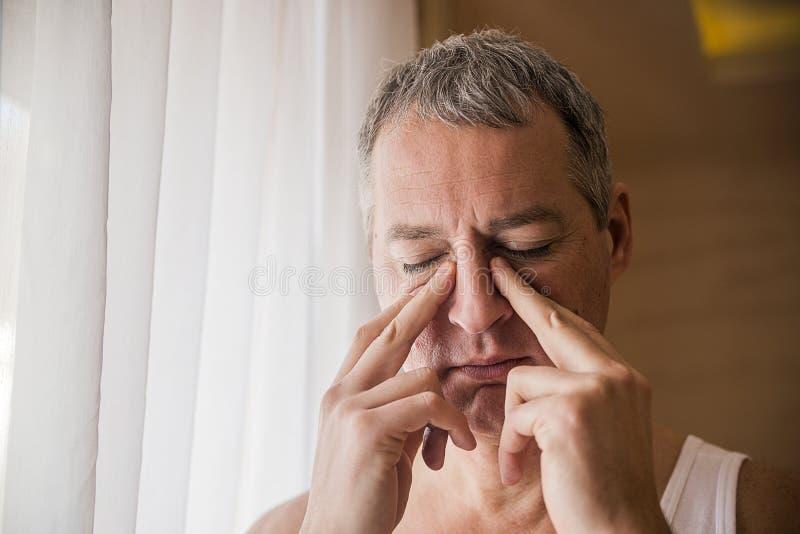 Smutny i przygnębiony mężczyzna trzyma jego głowę z jego ręką, stoi okno obraz stock