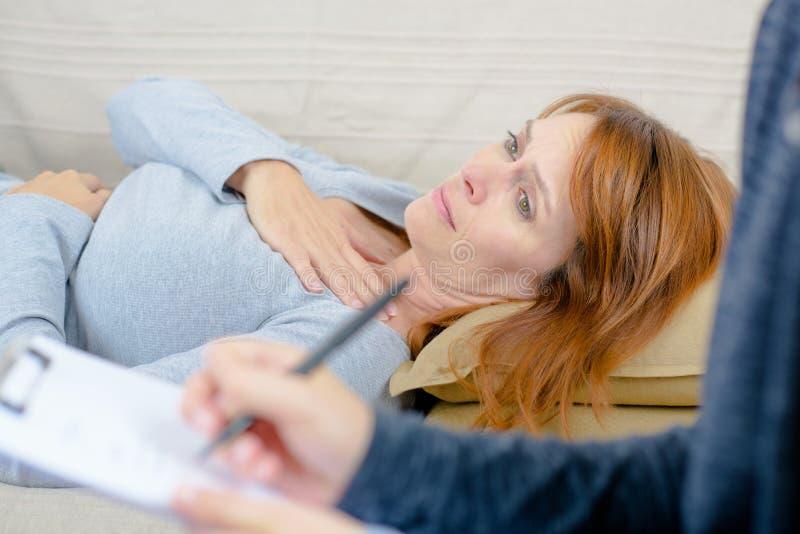 Smutny kobiety obsiadanie z terapeutą na kanapie w domu zdjęcie royalty free