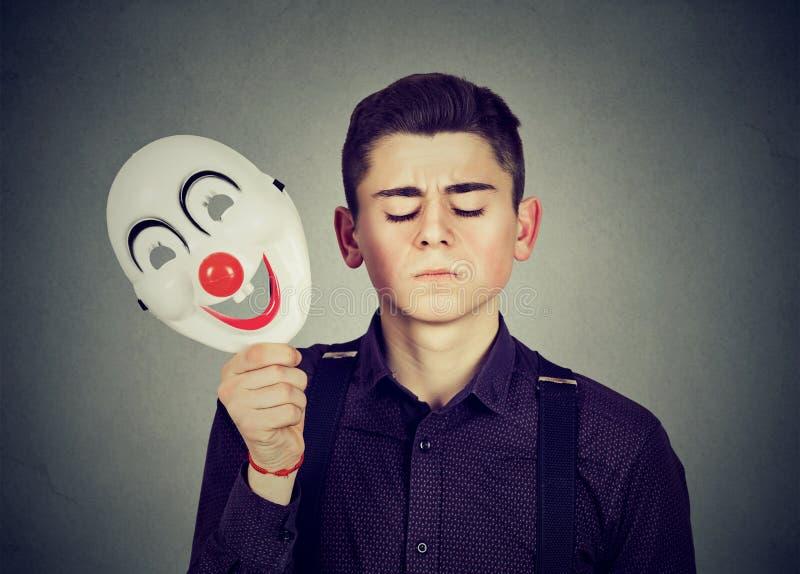 Smutny mężczyzna bierze daleko szczęśliwą błazen maskę Rozszczepiona osobowość zdjęcie royalty free