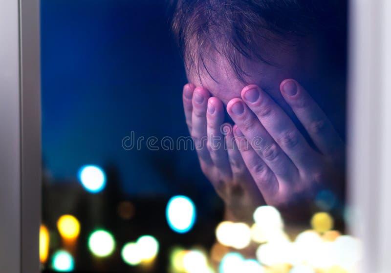 Smutny mężczyzna płacze póżno przy nocą okno zdjęcie stock