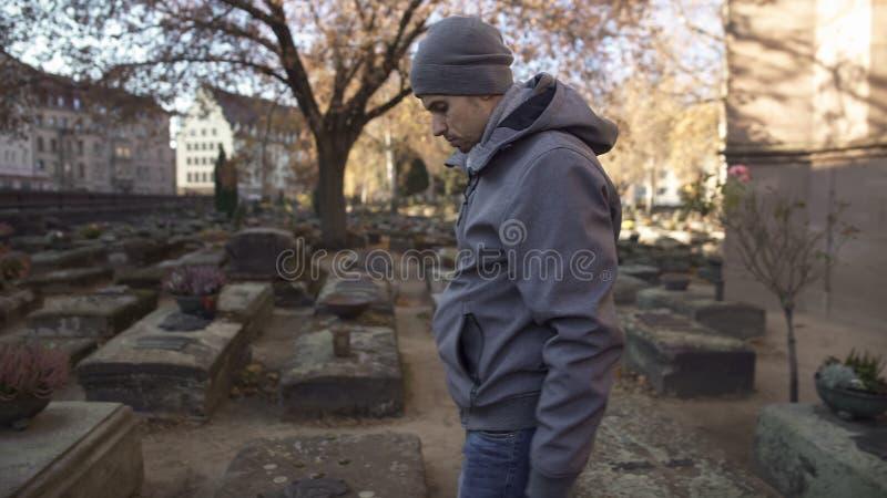 Smutny mężczyzna patrzeje grób na antycznym cmentarzu, upamiętnia rodziny, pokolenie obrazy royalty free