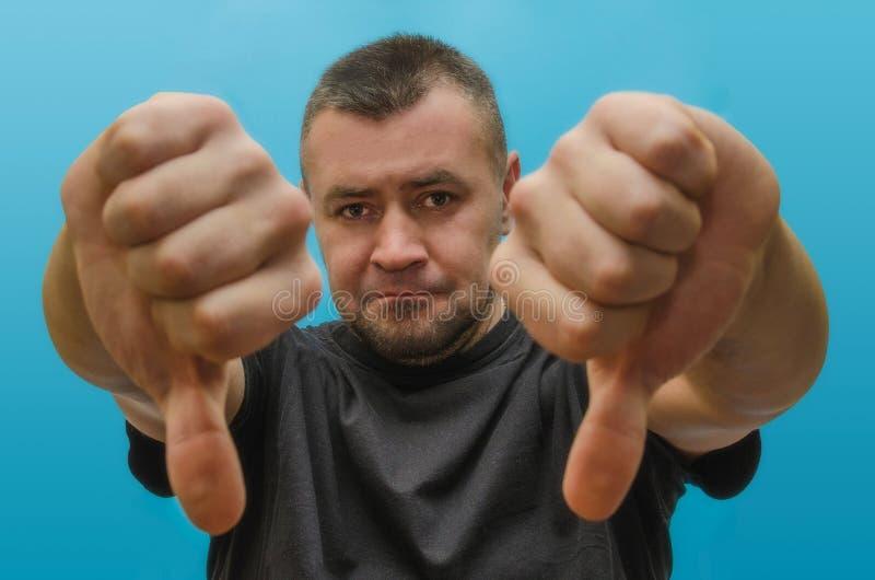 Smutny mężczyzna pokazuje kciuki zestrzela na błękitnym tle fotografia stock
