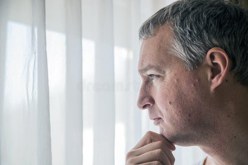 Smutny mężczyzna przyglądający out okno Czuciowy beznadziejny Przygnębiony dorośleć mężczyzna pozycję blisko okno zdjęcia royalty free