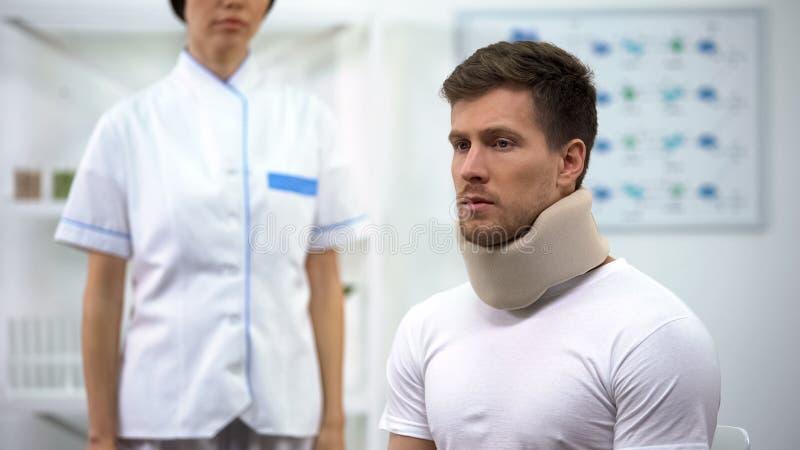 Smutny mężczyzna w piankowym karkowym kołnierzu przy lekarki spotkaniem, szyja uraz, napięcie fotografia stock