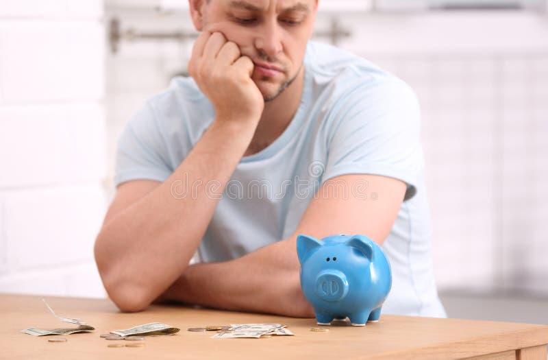 Smutny mężczyzna z prosiątko pieniądze i bankiem obraz royalty free