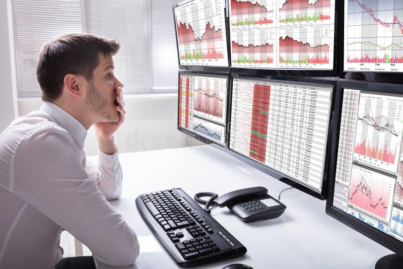 Smutny Męski operator Patrzeje wykresy Na Wieloskładnikowym ekranie komputerowym zdjęcia royalty free
