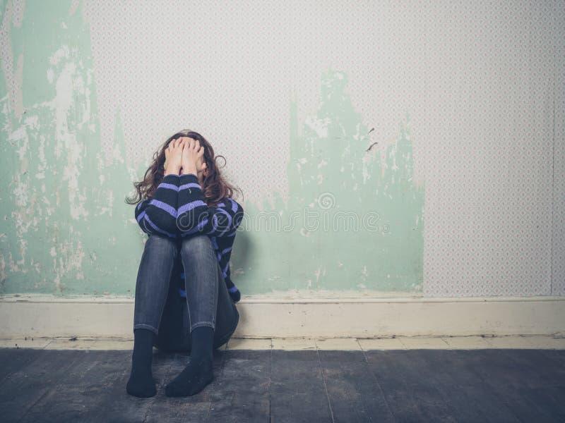Smutny młodej kobiety obsiadanie na podłoga w pustym pokoju obrazy stock