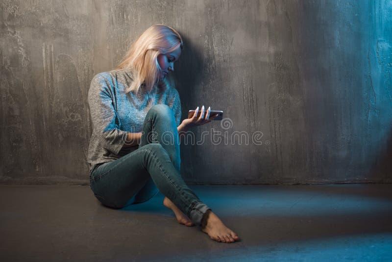 Smutny młodej kobiety obsiadanie na podłoga z telefonem w rękach Wywoławczy czekanie, żadny związek obrazy stock