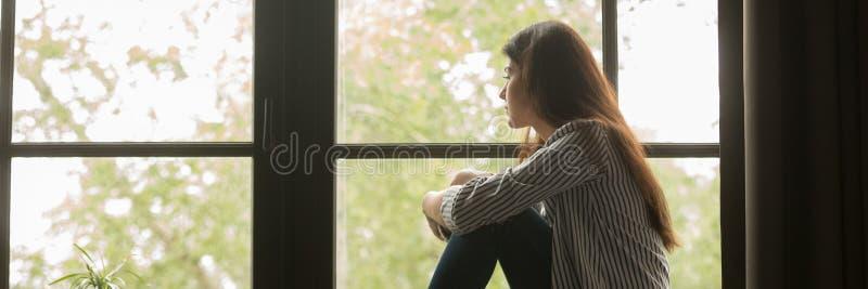 Smutny młodej kobiety siedzieć przyglądający za okno i główkowaniu zdjęcia royalty free