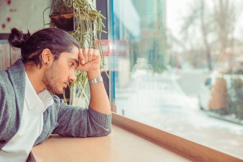 Smutny młody człowiek patrzeje w dół niepokojący, ręka na czole obrazy royalty free