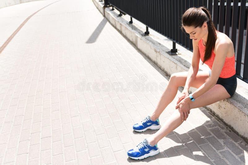 Smutny młodych kobiet odczuć ból w nodze zdjęcia stock