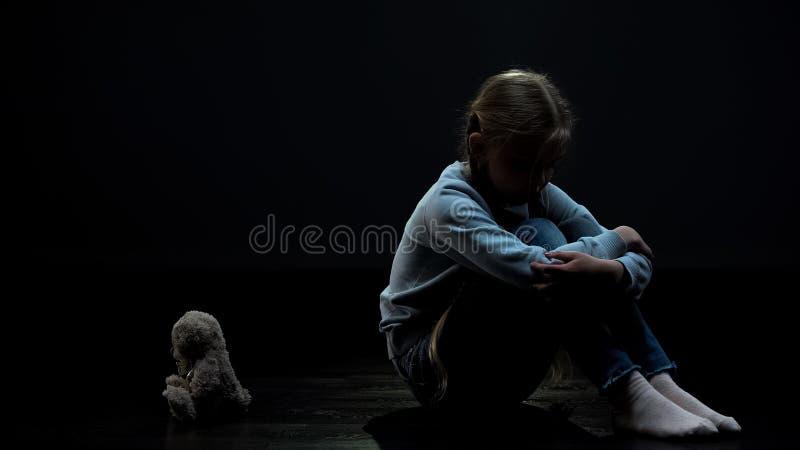 Smutny ma?ej dziewczynki czu? osamotniony, obsiadanie w ciemnym pokoju z powrotem mi? zabawka obraz stock
