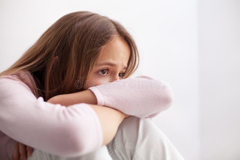 Smutny nastolatek dziewczyny obsiadanie na podłogowej podpiera głowie na jej kolanie fotografia stock