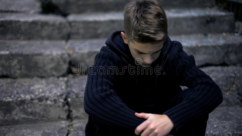 Smutny nastoletni obsiadanie na starych krakingowych krokach czuciowy żal i stroskanie, wychowywa stratę zdjęcie stock