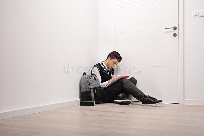 Smutny nastoletni studencki writing w notatniku indoors fotografia royalty free