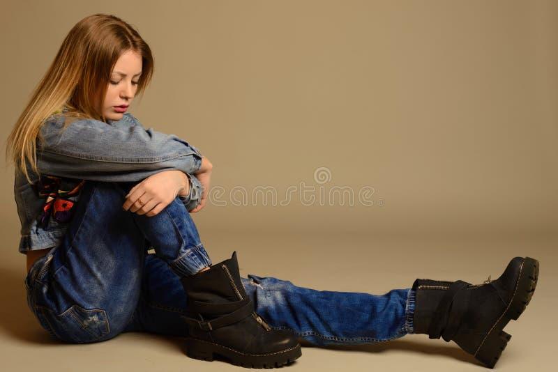 Smutny nastoletniej dziewczyny obsiadanie na podłoga cajgi, kurtka, buty zdjęcia royalty free