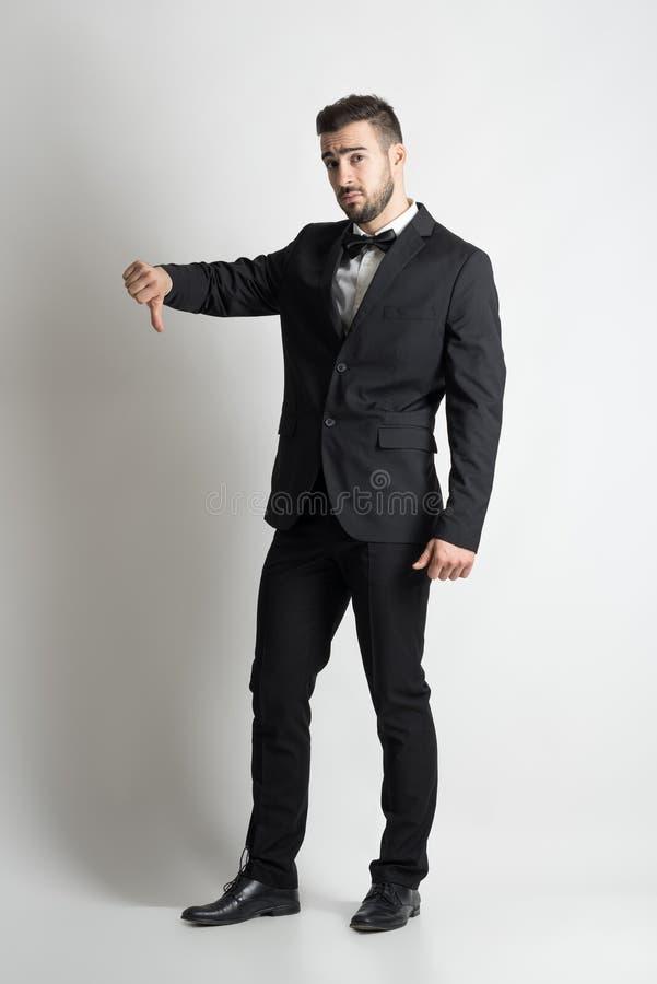 Smutny nierad fornal w kostiumu z łęku krawata seansu niechęci kciukami zestrzela ręka znaka obrazy royalty free