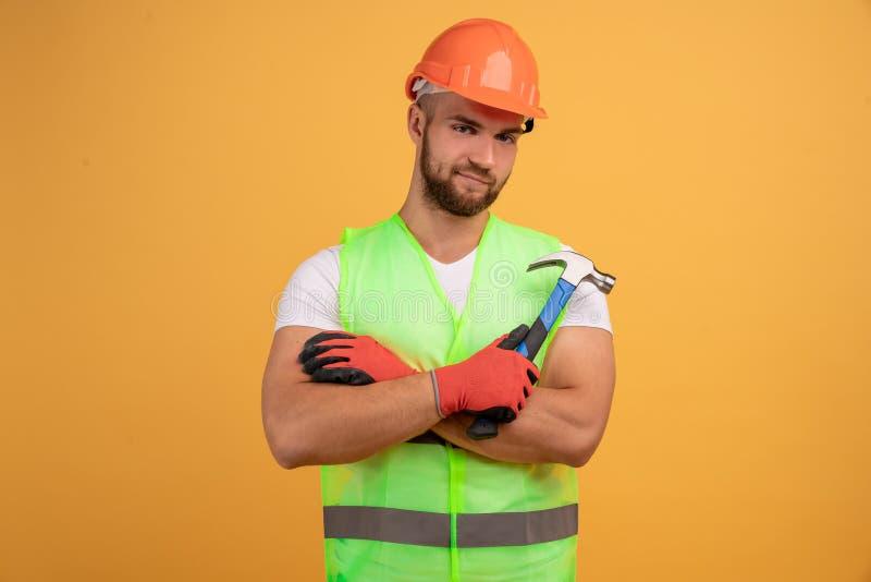 Smutny, nieszczęśliwy mężczyzna, który się zmęczył, trzyma ręce przekreślone, trzyma młotek w ręku, zmęczenie po naprawie i ręczn obraz stock