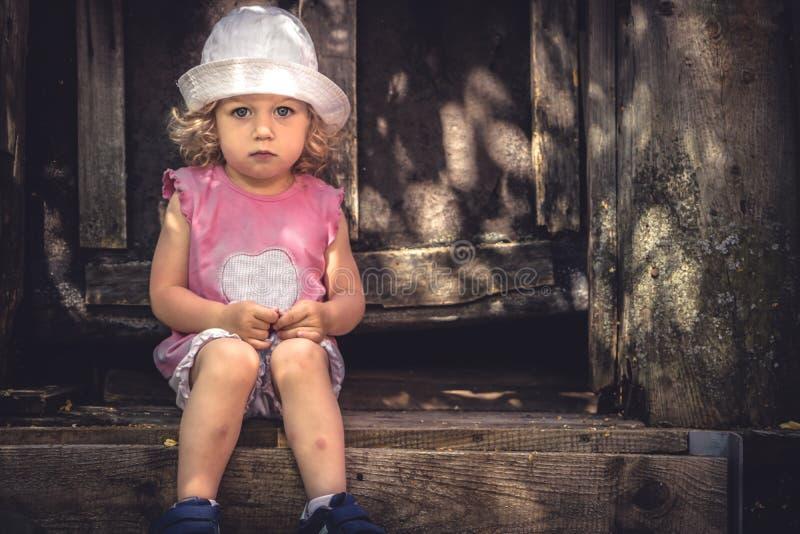 Smutny osamotniony dziecko dziewczyny spęczenia spojrzenia siedzieć osamotniony na drzwiowych kroków domu kopii starej przestrzen zdjęcia stock